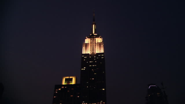 TD Empire State Building glowing at night / New York, New York, United States