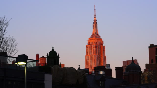 Empire State Building glows in sunset among the Manhattan cityscape.