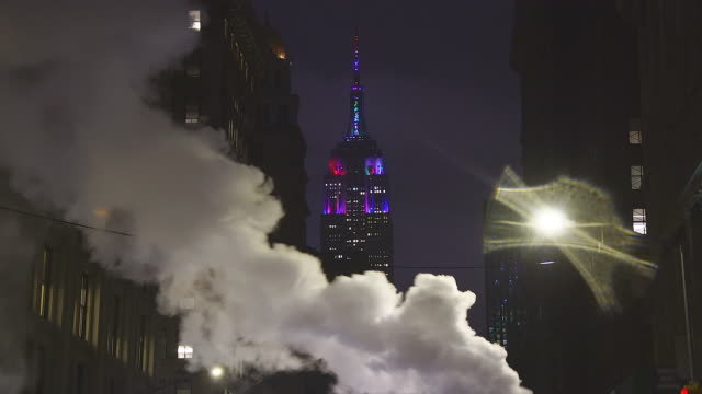 empire state building illuminations glow behind the drifting steam among the midtown manhattan buildings along the fifth avenue in the rainy night at new york usa in new year's eve during the winter holidays seasons on dec. 31 2018. - empire state building bildbanksvideor och videomaterial från bakom kulisserna