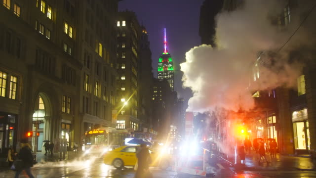 empire state building illuminations glow behind the drifting steam among the midtown manhattan buildings along the fifth avenue in the rainy night at new york usa in new year's eve during the winter holidays seasons on dec. 28 2018. - fifth avenue stock videos & royalty-free footage