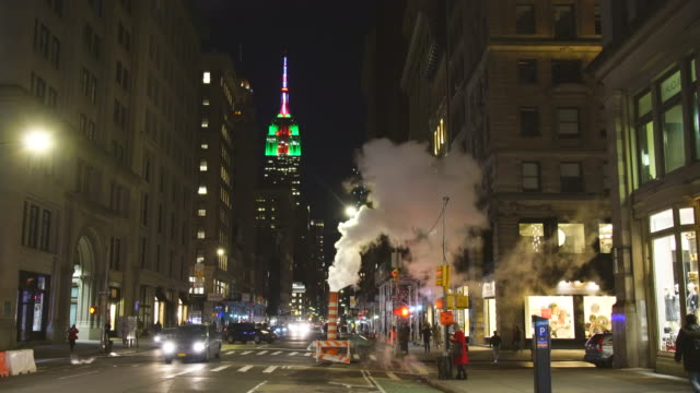 empire state building illuminations glow behind the drifting steam among the midtown manhattan buildings along the fifth avenue in the night at new york city usa in christmas holidays seasons usa on dec. 29 2018. - fifth avenue stock videos & royalty-free footage