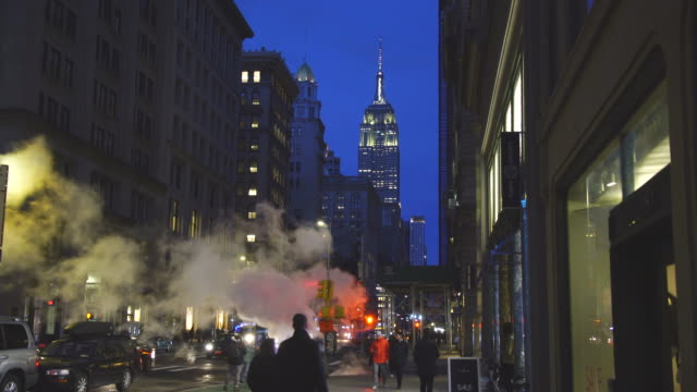 empire state building illuminations glow behind the drifting steam among the midtown manhattan buildings along the fifth avenue in the dusk at new york city usa in christmas holidays seasons usa on jan. 01 2019. - midtown manhattan stock videos & royalty-free footage