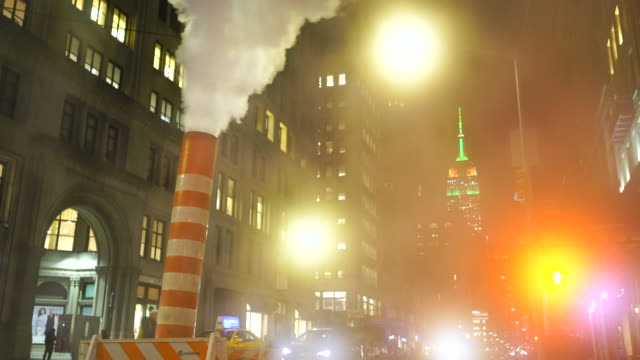 empire state building illuminations glow behind the drifting steam among the midtown manhattan buildings along the fifth avenue in the night at new york city usa in christmas holidays seasons usa on dec. 27 2018. - fifth avenue stock videos & royalty-free footage
