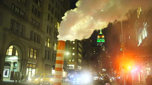 vidéos et rushes de empire state building illuminations glow behind the drifting steam among the midtown manhattan buildings along the fifth avenue in the night at new york city usa in christmas holidays seasons usa on dec. 27 2018. - signalisation routière lumineuse