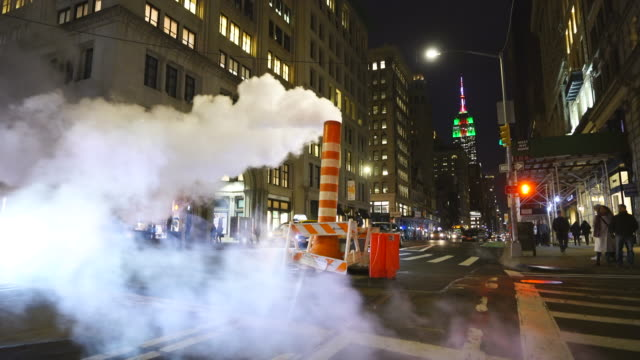 empire state building illuminations glow behind the drifting steam among the midtown manhattan buildings along the fifth avenue in the night at new york city usa in christmas holidays seasons usa on dec. 27 2018. - エンパイアステートビル点の映像素材/bロール