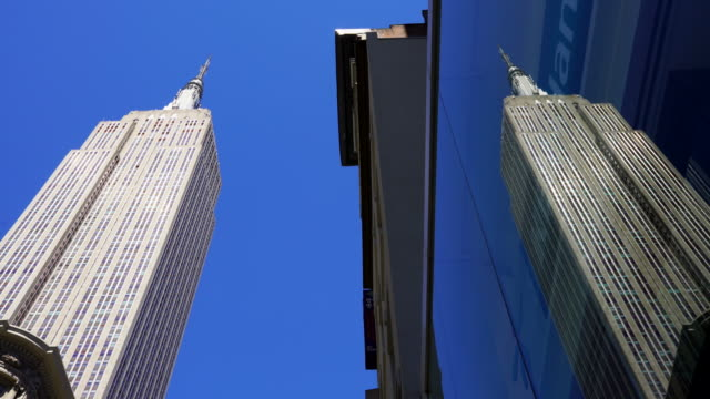 Empire State Building reflects to the building surface at Midtown Manhattan in New York City.