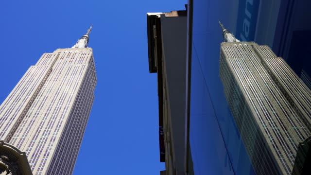 vídeos y material grabado en eventos de stock de empire state building reflects to the building surface at midtown manhattan in new york city. - empire state building