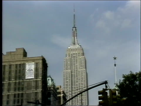 empire state building / traffic moves through intersection of 23rd street, broadway and fifth avenue / profile of female police officer wearing... - 1982年点の映像素材/bロール