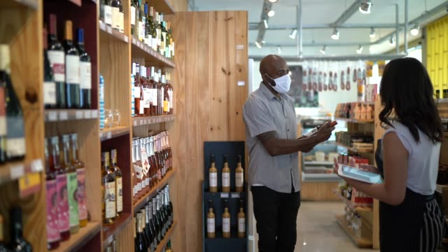employee and customer at wine store - using face mask - selling stock videos & royalty-free footage
