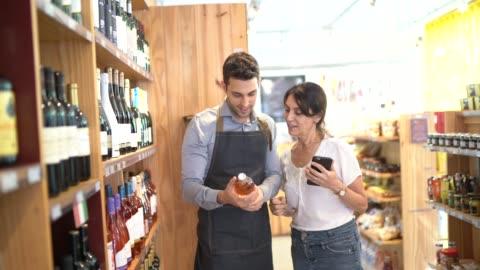 stockvideo's en b-roll-footage met medewerker en klant bij wijnwinkel - klanten georiënteerd