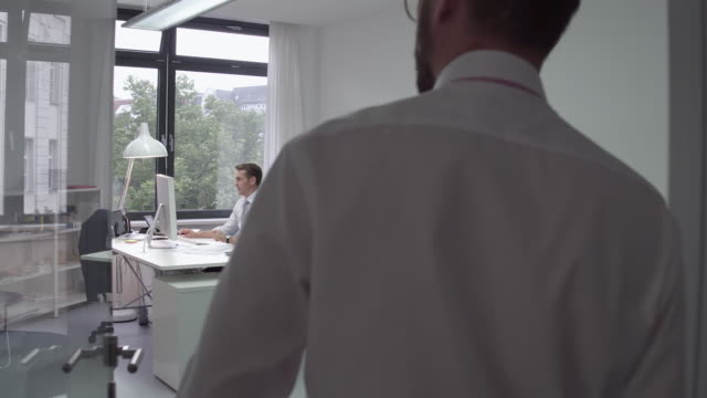 employee approaching manager in his office and shaking hands