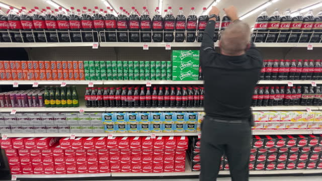 employee arranging coca-cola bottles on store shelf in harmon grocery store in orem. coca cola is scheduled to announce their fourth-quarter 2020... - orem utah stock videos & royalty-free footage
