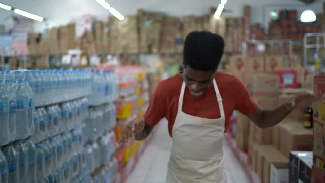 vídeos de stock, filmes e b-roll de empregado que comemora e que dança no supermercado - cultura jovem