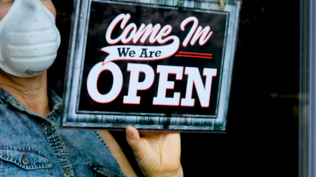 employee changing the sign on closed business to open business - sign stock videos & royalty-free footage