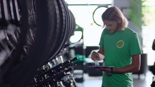 stockvideo's en b-roll-footage met employee checks price tags on new bikes in stock and enters data on tablet computer - north carolina amerikaanse staat