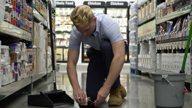 vídeos de stock, filmes e b-roll de employee clearing away a broken jar in a warehouse supermarket - ajoelhando se