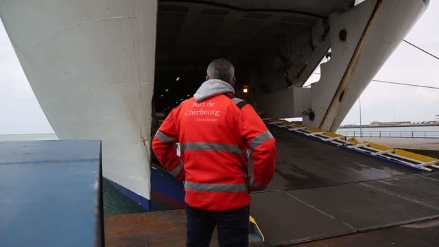 employee controlling loading goods into cargo ship at port of cherbourg, linking france with uk. the cost of shipping goods from france to britain... - rear view stock videos & royalty-free footage