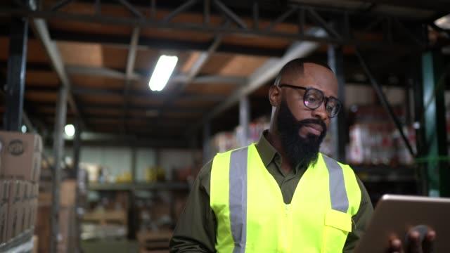 vidéos et rushes de employé faisant un appel vidéo sur la tablette numérique à l'entrepôt / industrie - lieu de travail