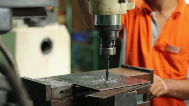 vidéos et rushes de drilling machine, employee drilling machine in flat steel plate with bench drill. - pushing