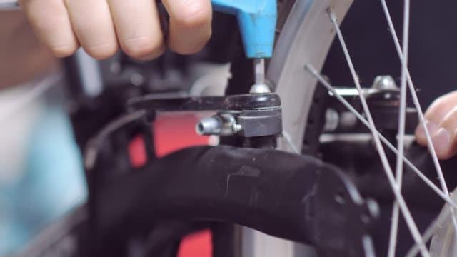 anställd i en cykelaffär dra åt en skruv med en hexagon medan du gör en reparation - employee bildbanksvideor och videomaterial från bakom kulisserna