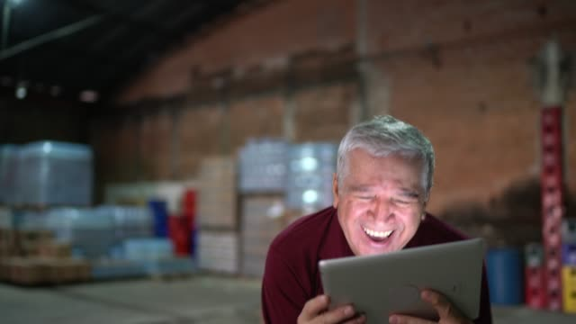 employee in a warehouse dancing and celebrating holding a digital tablet - warehouse stock videos & royalty-free footage