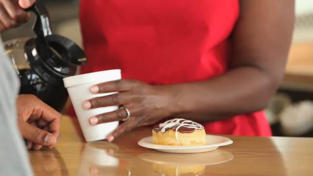 cu pan focus employee in donut shop pouring coffee into disposable cup and taking money from customer at counter/ richmond, virginia, usa - doughnut stock videos and b-roll footage