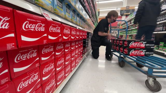 employee in face mask arranging boxes with coca-cola on store shelf at harmon grocery store. coca cola is scheduled to announce their fourth-quarter... - orem stock videos & royalty-free footage