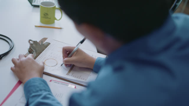 cu employee makes notes on a document during a business meeting - produced segment stock videos & royalty-free footage