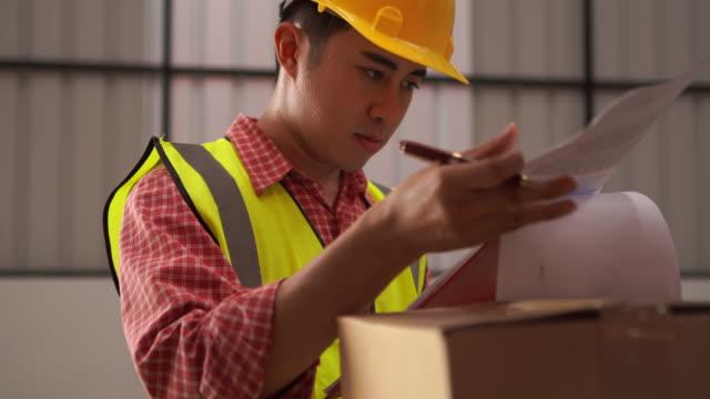 vídeos y material grabado en eventos de stock de empleado hombre con sombrero duro usando walkie-talkie verificando inventario en la tienda del almacén - paleta herramientas industriales