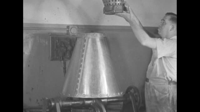 stockvideo's en b-roll-footage met employee moves suspended coneshaped metal basket full of coins over cone shaped vat / two shots of man releasing coins from basket into vat / man... - amerikaanse munt
