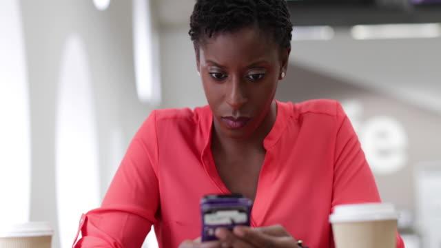 Employee on coffee break using her smartphone