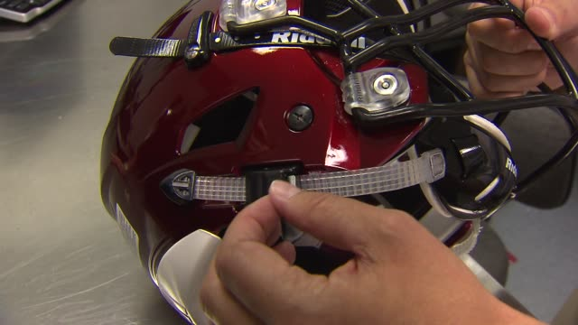 WGN Employee points out new chin strap design on football helmet at a Riddell testing lab in Rosemont Ill
