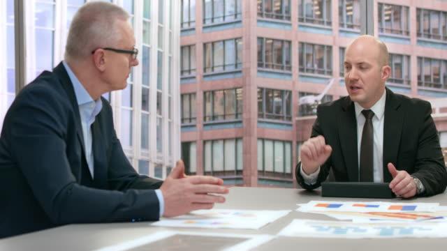 Medarbetare presentera några grafer till en senior business man vid ett möte