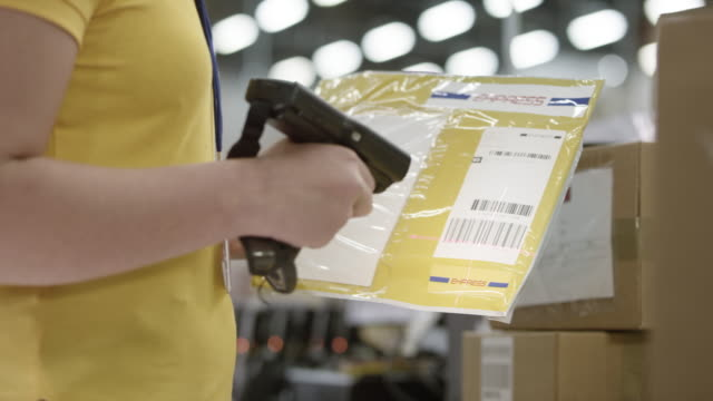 Employee scanning  large envelopes for express mail with a handheld barcode scanner