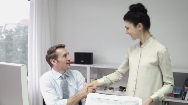 employee shaking hands with manager and leaving his office