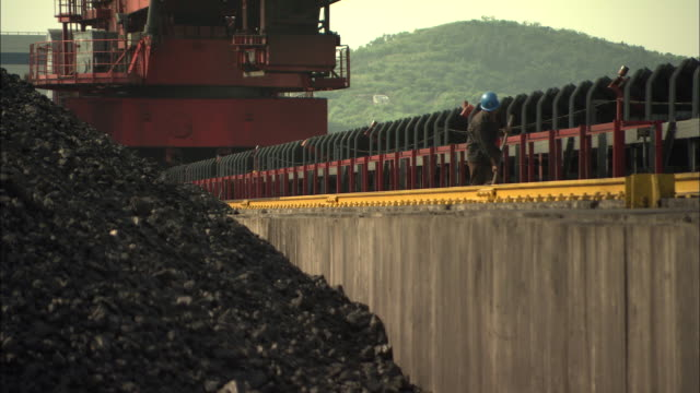 ws employee shoveling lose coals back onto pile at huaneng yuhuan ultra supercritical power plant, yuhuan county, zhejiang, china - coal fired power station stock videos & royalty-free footage