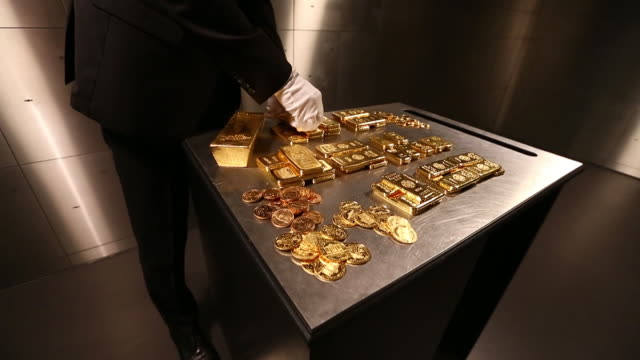 employee showing gold bars fine gold and gold coins inside of precious metals vault at pro aurum kg munich bayern germany on wednesday july 10 2019 - mid section stock videos & royalty-free footage