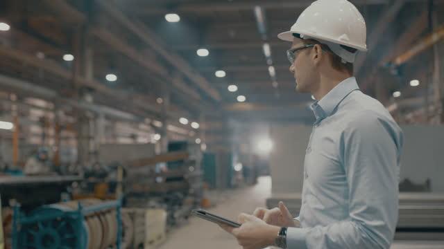 slo mo mitarbeiter mit einem digitalen tablet in einer produktionsanlage - analysing stock-videos und b-roll-filmmaterial