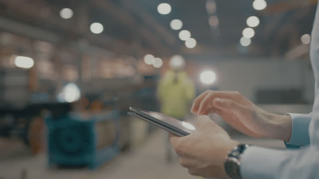 slo mo employee using a digital tablet in the factory - using digital tablet stock videos & royalty-free footage