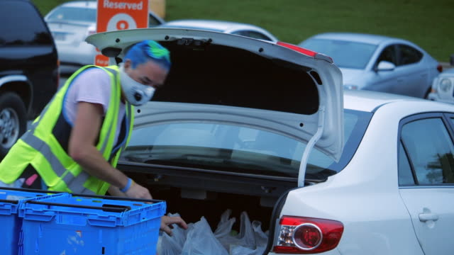 vidéos et rushes de employee wearing face mask is helping the pick up service at the walmart super shopping center in the early morning in north georgia, usa, during the 2020 global covid-19 pandemic - denrée périssable