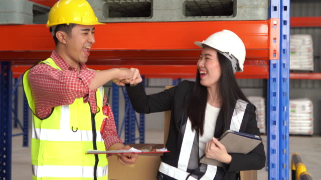 employee woman and man in hard hat use digital teblet for checking inventory in warehouse store , success ,  hand greeting ,fist bump - saluting stock videos & royalty-free footage