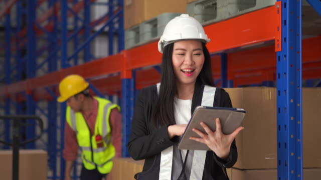 employee woman in hard hat use laptop and makes notes in notepad on background of warehouse worker - authority stock videos & royalty-free footage