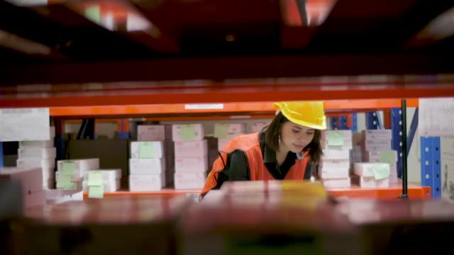 stockvideo's en b-roll-footage met de vrouw die van de werknemer de lezer van de streepjescode voor het controleren van voorraadproduct in pakhuislogistiek gebruikt. - etiket