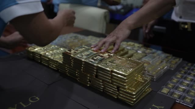 Employees arranges one kilogram gold bars at the YLG Bullion International Co headquarters in Bangkok Thailand on Wednesday Jan 13 Employees hands...