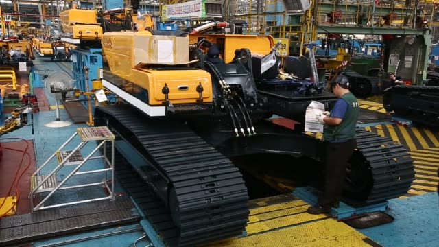 Employees assemble excavators on the production line at the Hyundai Heavy Industries Co Plant in Ulsan South Korea on Wednesday July 29 2015 Shots...