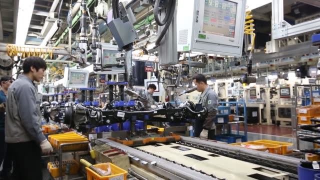 employees assemble vehicle chassis modules on a production line at the hyundai mobis co factory in asan south chungcheong south korea on tuesday jan... - fahrgestell stock-videos und b-roll-filmmaterial