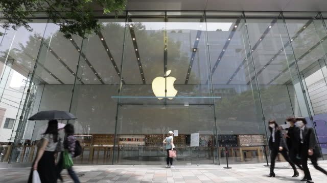 employees assist customers, all wearing protective masks, while waiting in line outside apple inc. stores in the omotesando and shibuya districts of... - apple computer stock-videos und b-roll-filmmaterial