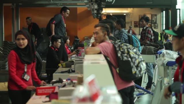 Employees assist customers at AirAsia Bhd checkin counters at Kuala Lumpur International Airport 2 in Sepang Selangor Malaysia on Thursday May 25 2017