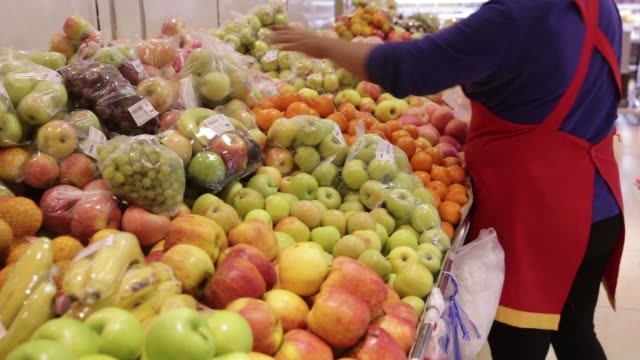 Employees assist customers at the fruit section of a Sansar Supermarket in Ulaanbaatar Mongolia on Wednesday July 13 An employee arranges fruit on a...