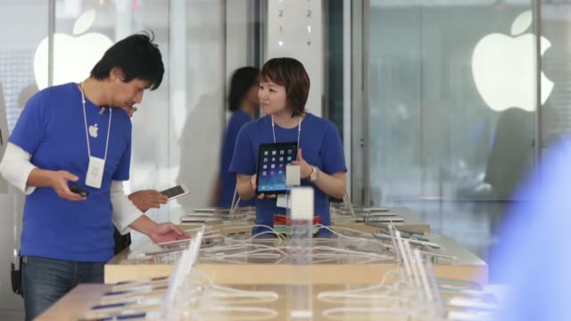 vídeos de stock e filmes b-roll de employees assist customers purchasing the apple inc ipad air at the company's store in the ginza district of tokyo japan on friday nov 1 an employee... - dentro